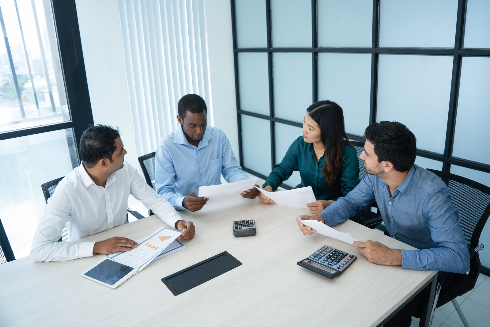 Four employees sitting at table having a business meeting